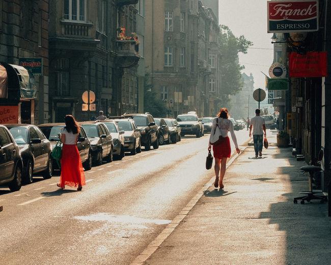 People walking on road along buildings