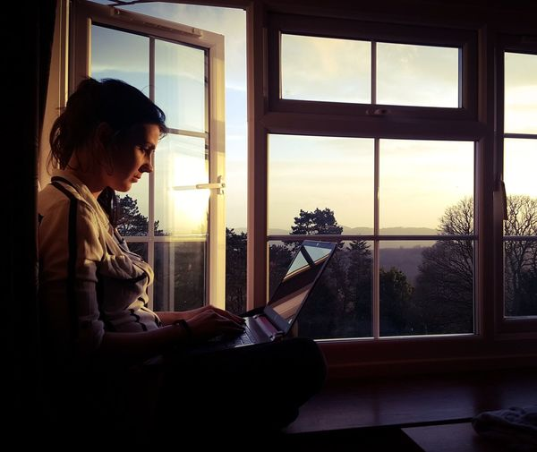 Woman Using Laptop While Sitting On Window Sill