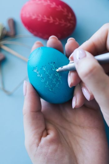 Cropped Hands Of Woman Drawing On Blue Easter Egg