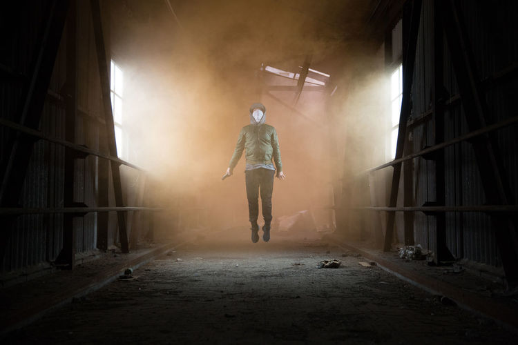Full Length Of Man Holding Distress Flare While Jumping In Abandoned Workshop