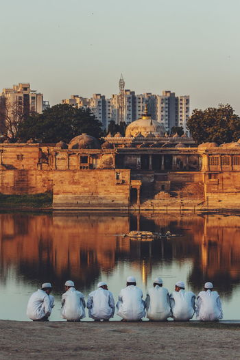 View of birds in lake against cityscape
