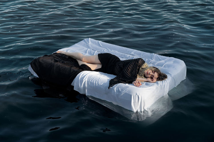 High angle view of woman sleeping on mattress in sea