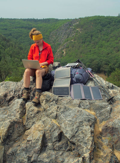caucasian female hiker sitting on a rock while working on a laptop being charged by solar panels nearby, portable solar charing technology concept Backpacking Camping Charing Cross Freedom Hiking Nature Sitting Solar Panel Tablet Travel Trekking Woman Working Activity Adventure Battery Beauty In Nature Casual Clothing Communication Connection Day Female Full Length Internet Laptop Leisure Activity Lifestyles Mountain Nature Navigation One Person Outdoors People Portable Information Device Real People Rock Rock - Object Sitting Solid Technology Wireless Technology Young Adult