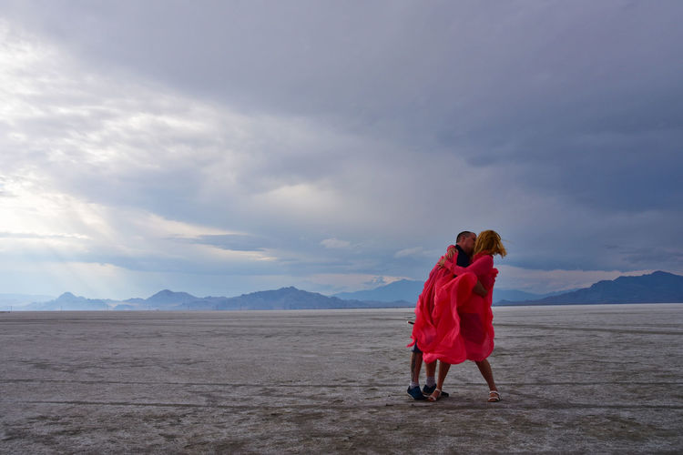 Full Length Of Couple Kissing While Standing On Ground Against Sky