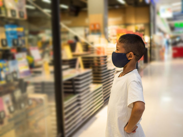 Side view of boy looking at store