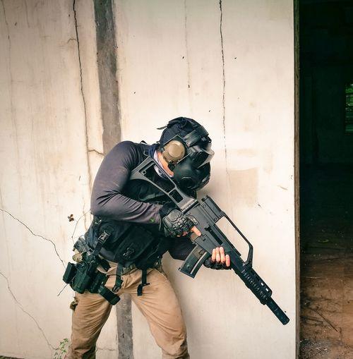 Man with machine gun standing by doorway