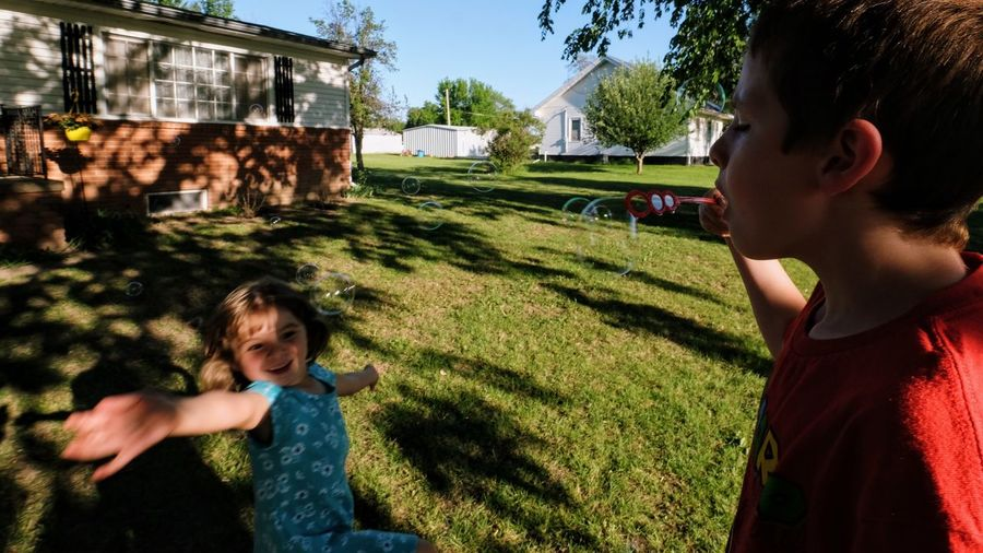 Side view of boy blowing bubbles while sister dancing at yard