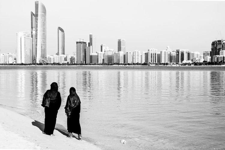 Muslim women standing on beach