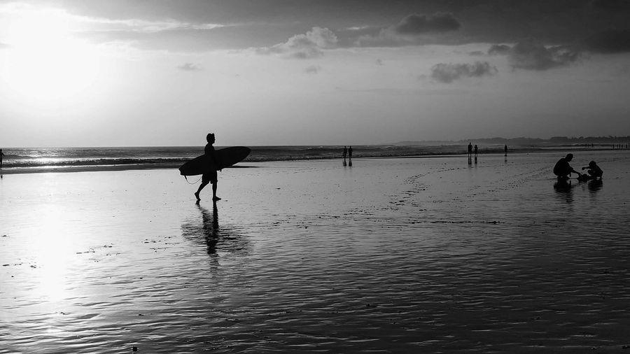 Silhouette Surfer Walking On Calm Beach