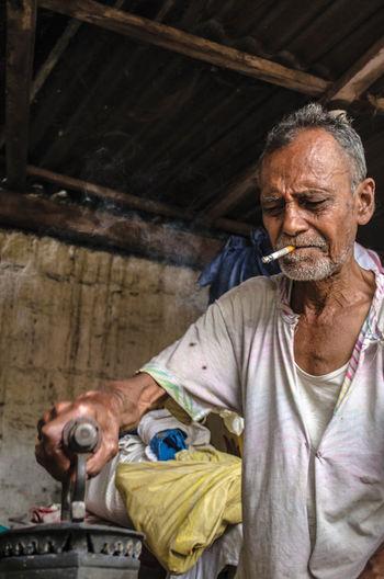 Mature Man Smoking Cigarette While Ironing