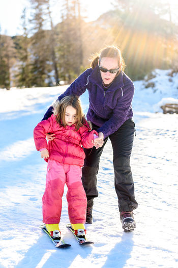 View Of Mother With Daughter Standing In Snow