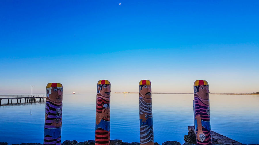 Lifeless Beauty In Nature Blue Bollards Calm Day Nature No People Outdoors Pole Scenics Sky Tranquil Scene Tranquility Water Wooden Post