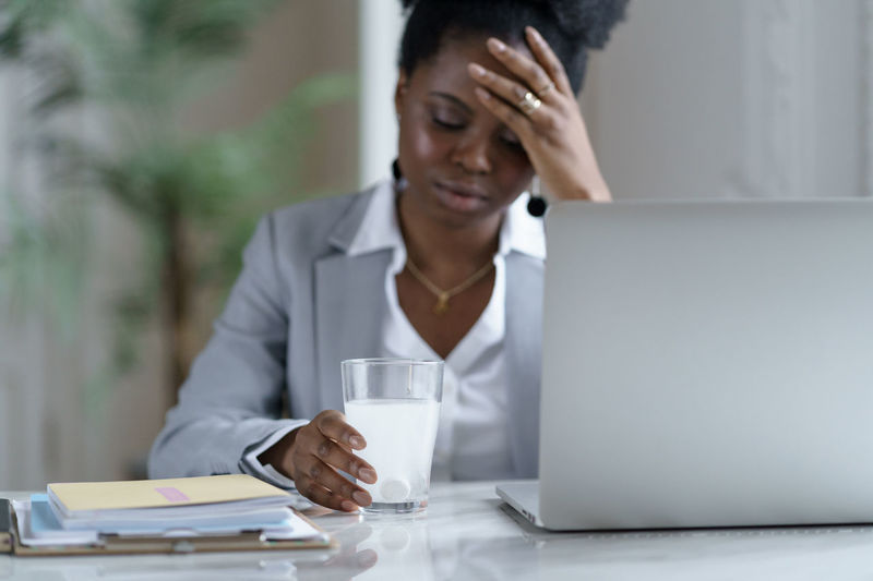 Ill woman holding glass with medicine by laptop on table
