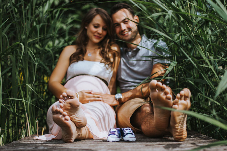 Husband and pregnant wife sitting with shoes amidst plants