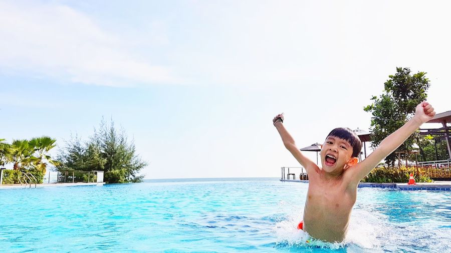 Portrait of smiling boy in swimming pool against sky