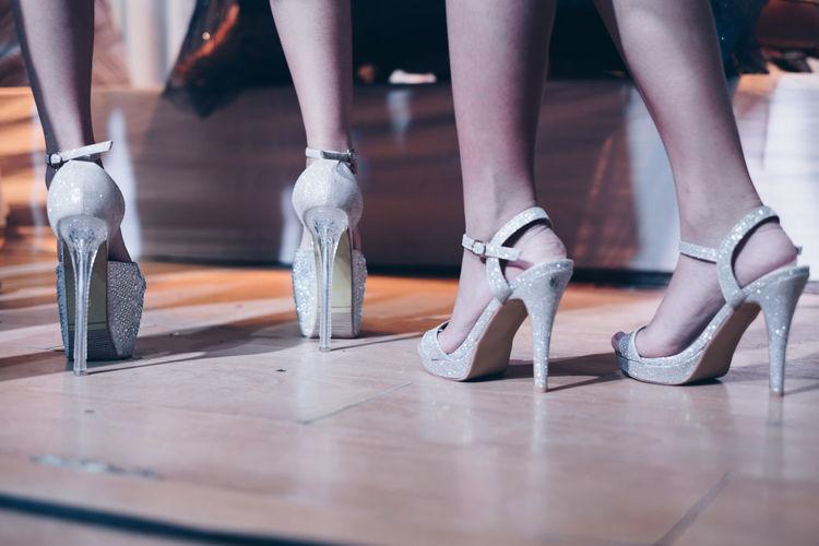 Low Section Of Women In High Heels Standing On Floor