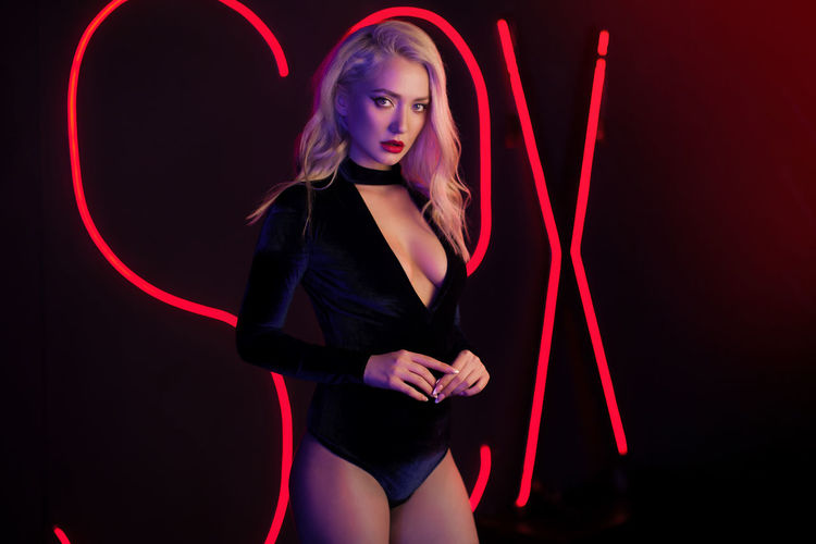 Fashion art photo of elegant blonde model in seductive wear with light neon colored club spotlights Adult Beautiful Woman Beauty Black Background Contemplation Fashion Front View Hairstyle Illuminated Indoors  Light Light - Natural Phenomenon Neon Night Nightlife One Person Red Standing Studio Shot Three Quarter Length Women Young Adult Young Women