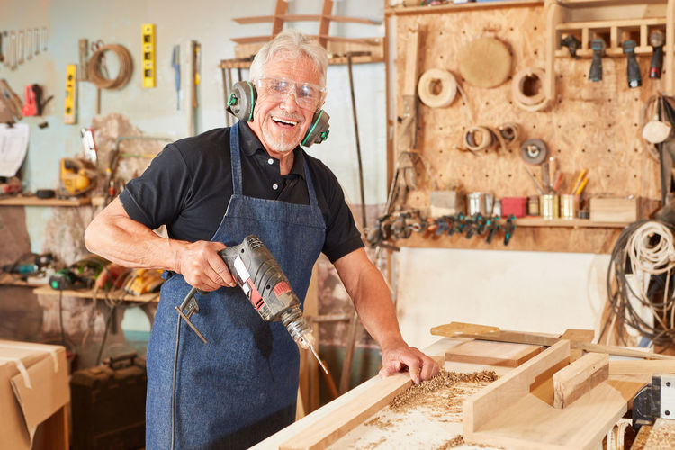 Portrait of senior carpenter holding drill at workshop