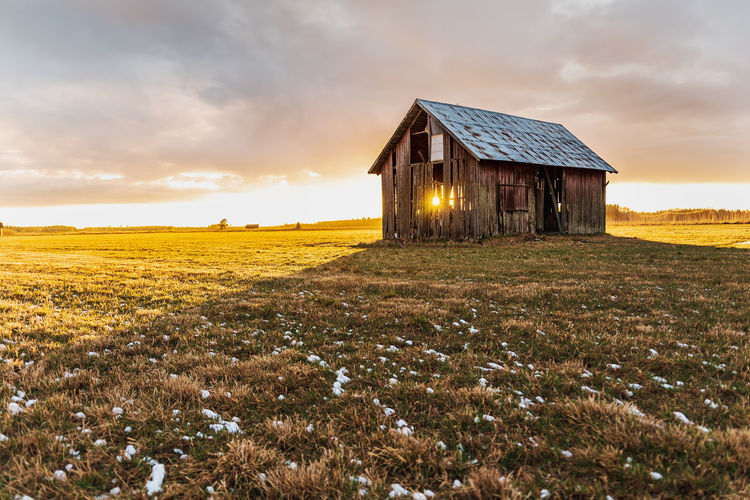 Barn on field against sky during sunset