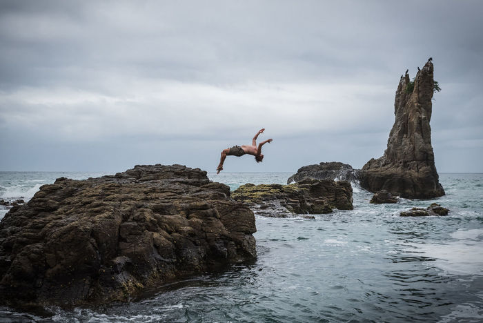A friend flips off a large rock into the ocean near Kiama, Australia. Australia Backflip Weekend Adventure Jumping Leisure Activity Mid-air Motion Capture One Person Outdoors Rock Rock Formation Sky Sport Water Week On Eyeem Be Brave A New Beginning A New Perspective On Life