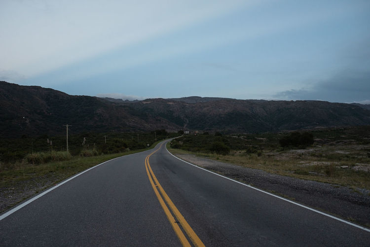 Road Transportation Road Marking Symbol Marking Mountain Sign Sky Direction The Way Forward No People Nature Environment Non-urban Scene Landscape Beauty In Nature Scenics - Nature Double Yellow Line Diminishing Perspective Tranquility Mountain Range Outdoors Dividing Line Long