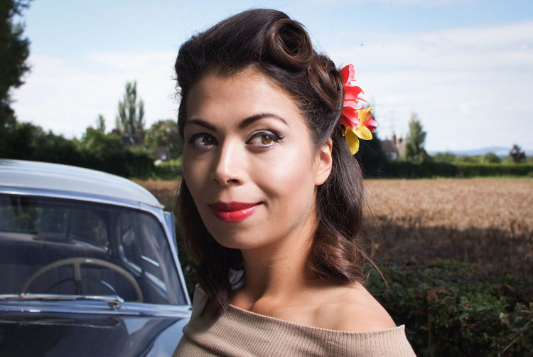 Close-Up Of Smiling Woman By Vintage Car Against Sky