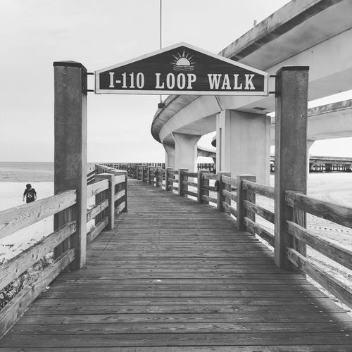 Low angle view of information sign on pier at beach against sky