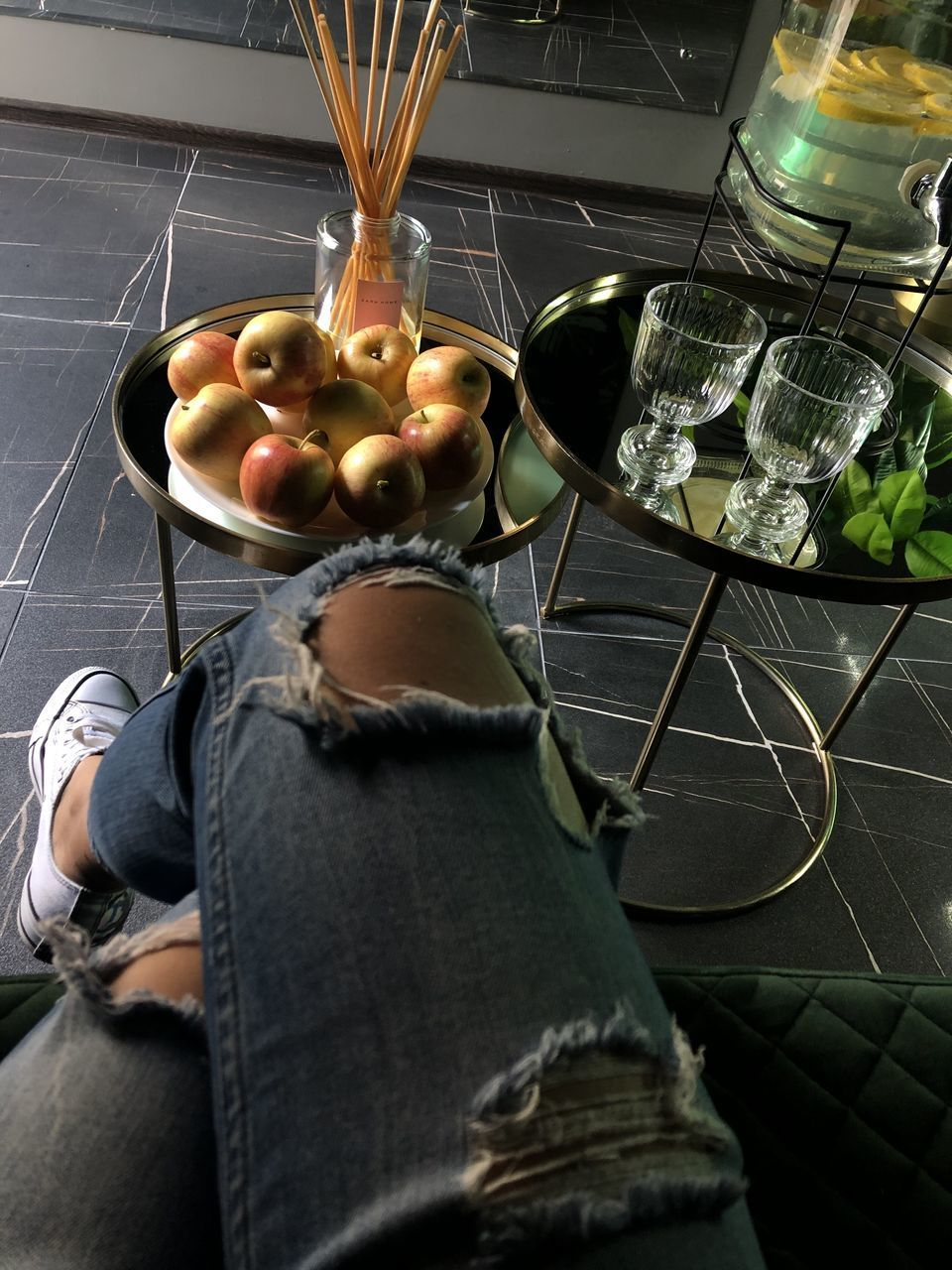 real people, one person, human body part, food and drink, lifestyles, indoors, food, healthy eating, body part, fruit, human leg, low section, freshness, wellbeing, men, high angle view, vegetable, casual clothing, personal perspective, human foot, jeans