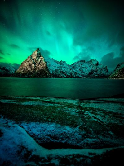 Scenic view of aurora borealis over sea against sky at night