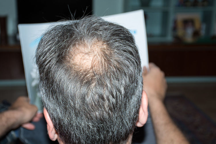 Rear view of man reading paper