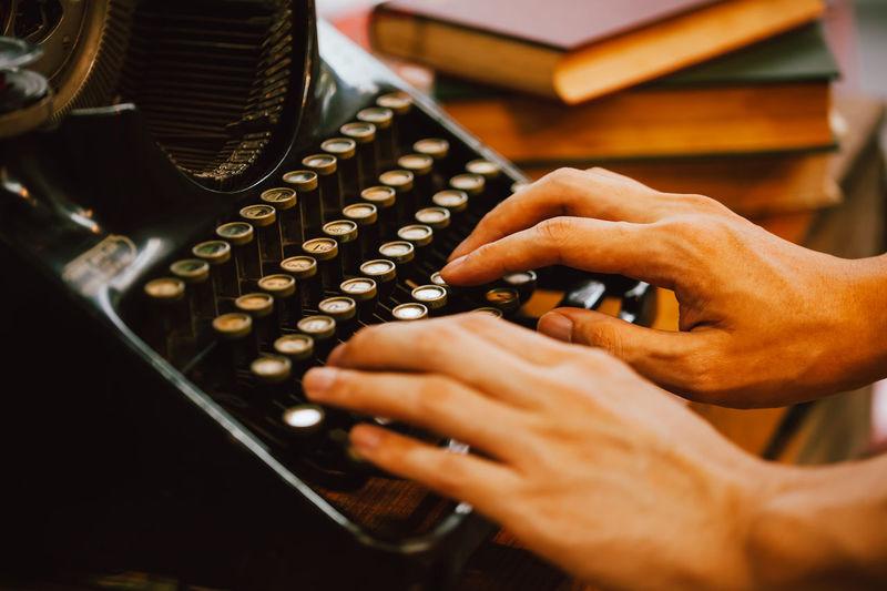 Cropped hands of man using typewriter