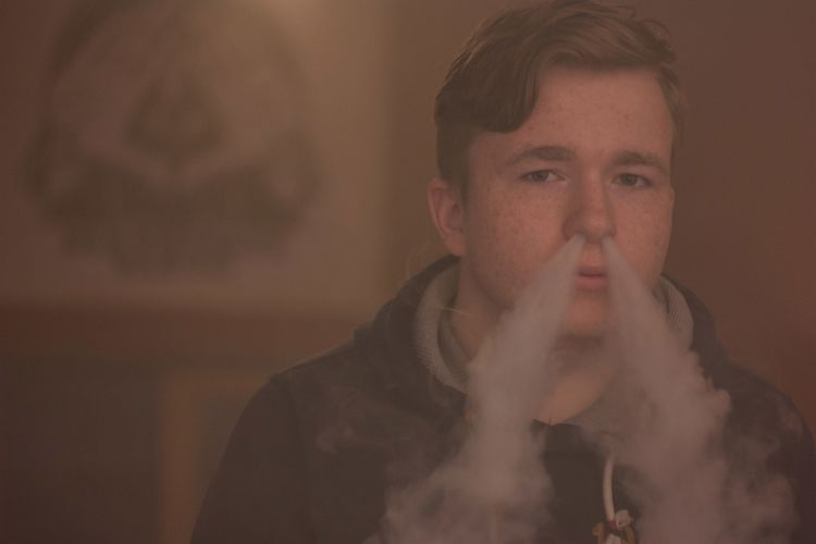 Portrait of man emitting smoke from nose