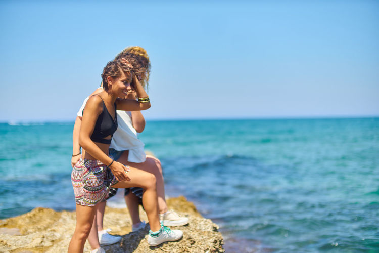 Young women standing on rock at beach against clear blue sky