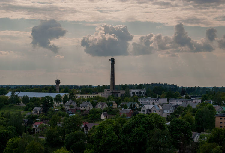Smoke stack and houses in town against sky