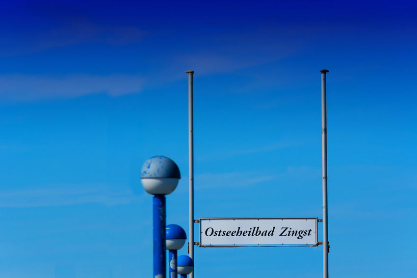 The pier with a diving bell in Zingst / Germany Blue Text Sky Communication Western Script No People Sign Street Light Low Angle View Street Lighting Equipment Pole Day Guidance Outdoors Nature Clear Sky Architecture Technology Information Light