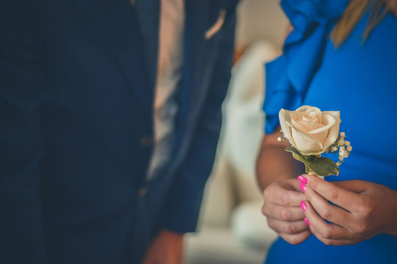 Close-up of woman holding rose while standing by man