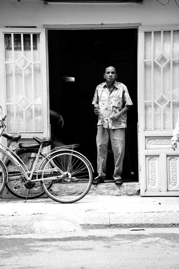Full length portrait of young man standing against bicycle