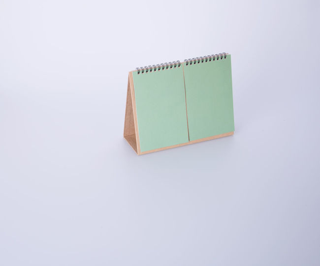 High angle view of blank green desk calendar against white background