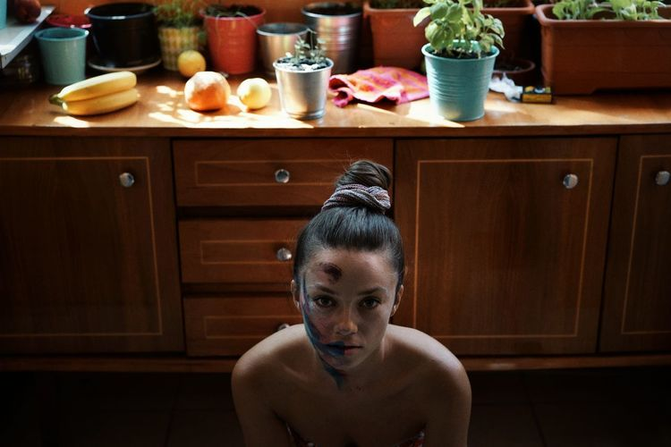 High Angle Portrait Of Shirtless Young Woman With Messy Make-Up Sitting In Kitchen At Home