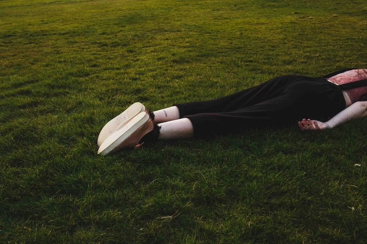 Low section of woman lying on grass