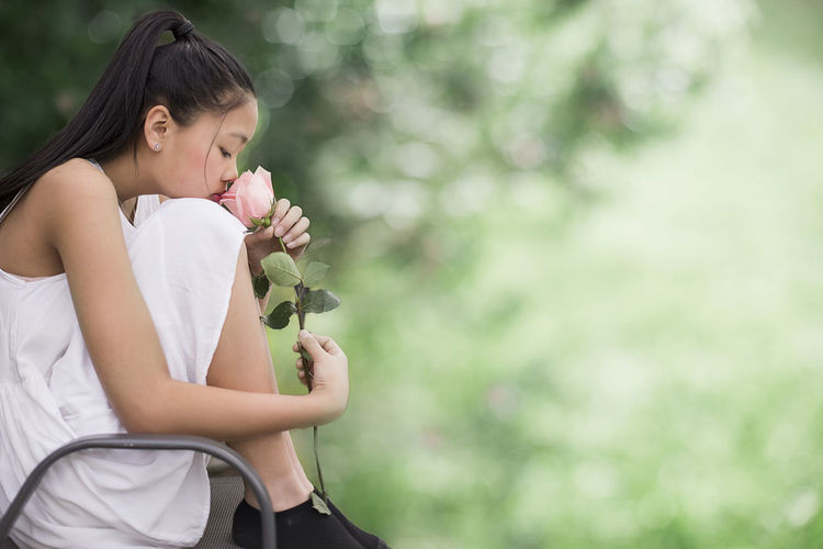Side view of woman smelling rose at park