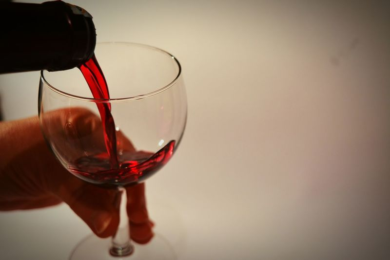 Cropped Hand Pouring Red Wine In Glass Against Wall