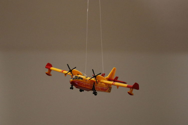 Toy airplane hanging against gray background