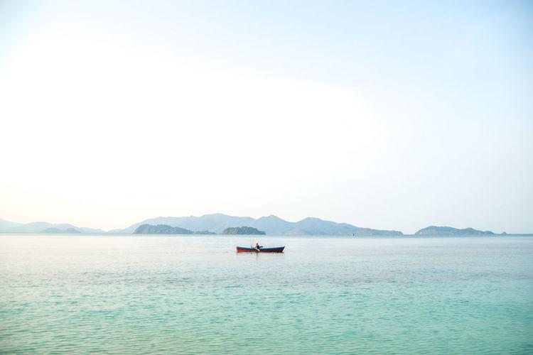 Man Boating In Sea Against Sky