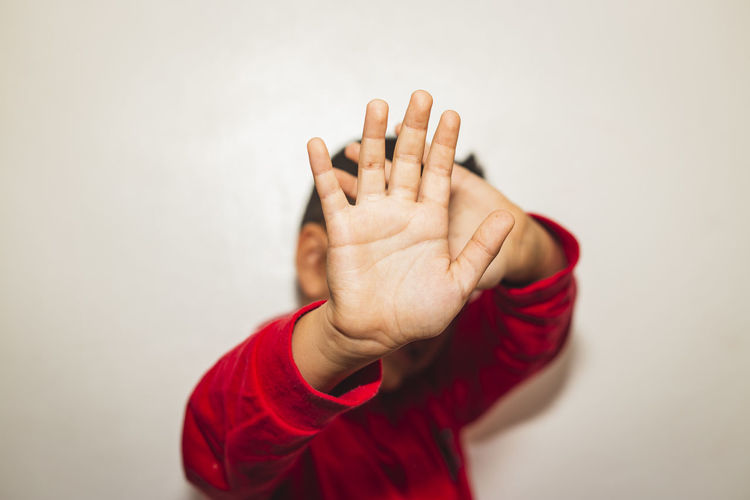 Boy showing stop gesture against white background
