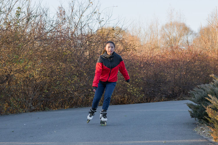 Young Woman Roller Skating On Road