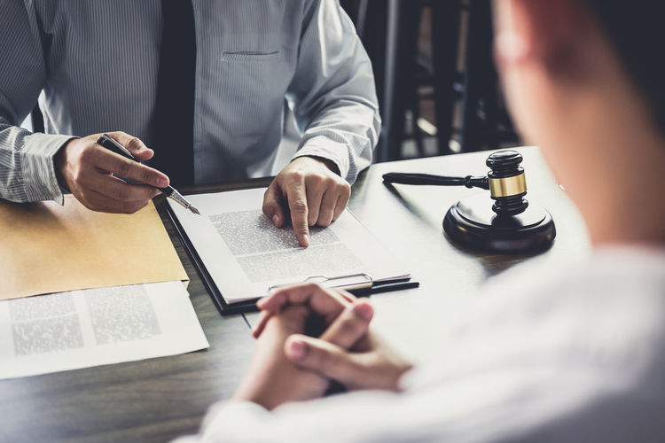 Midsection of judge pointing at document while worried client sitting on table