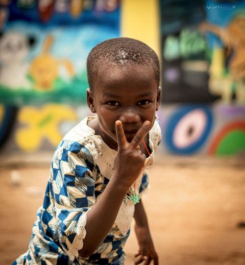 Portrait of boy gesturing peace sign in village