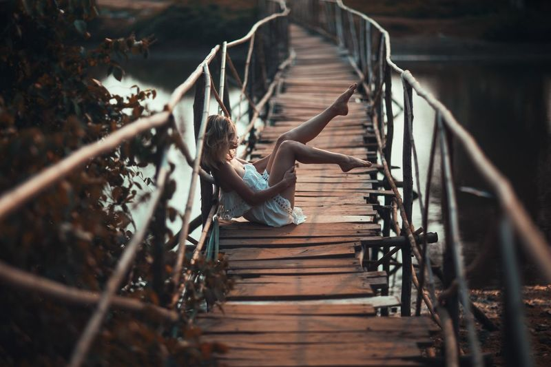 Side view of woman sitting on wooden footbridge