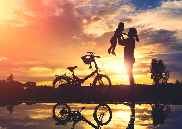 Silhouette of mother and daughter with bicycle against sky during sunset